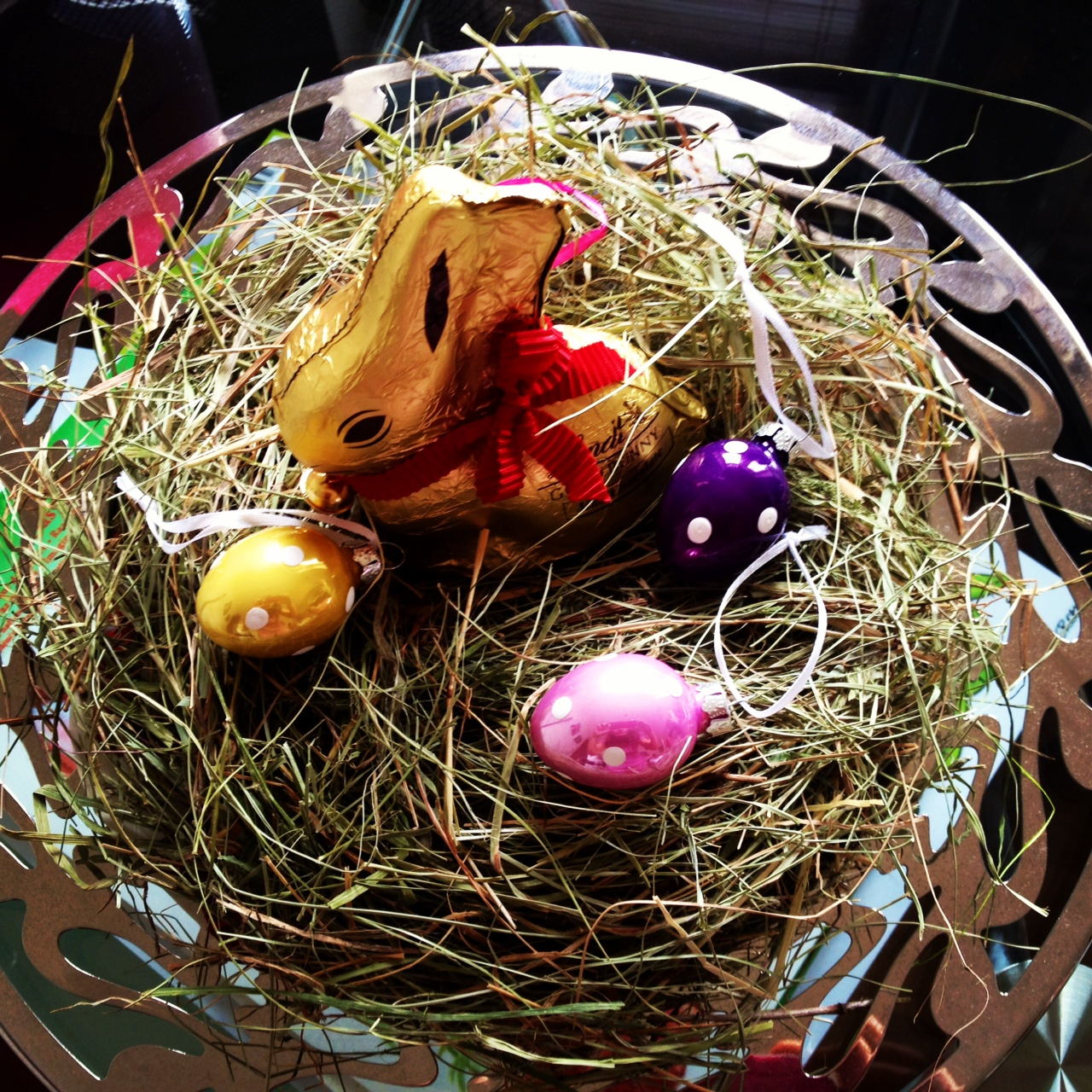 Lindt bunny nestled into easter grass on an Alessi plate