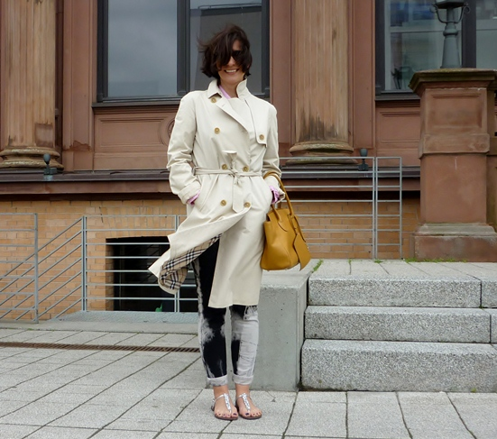 Rebel pairing a classic trench coat with distressed denim and open toe sandals.