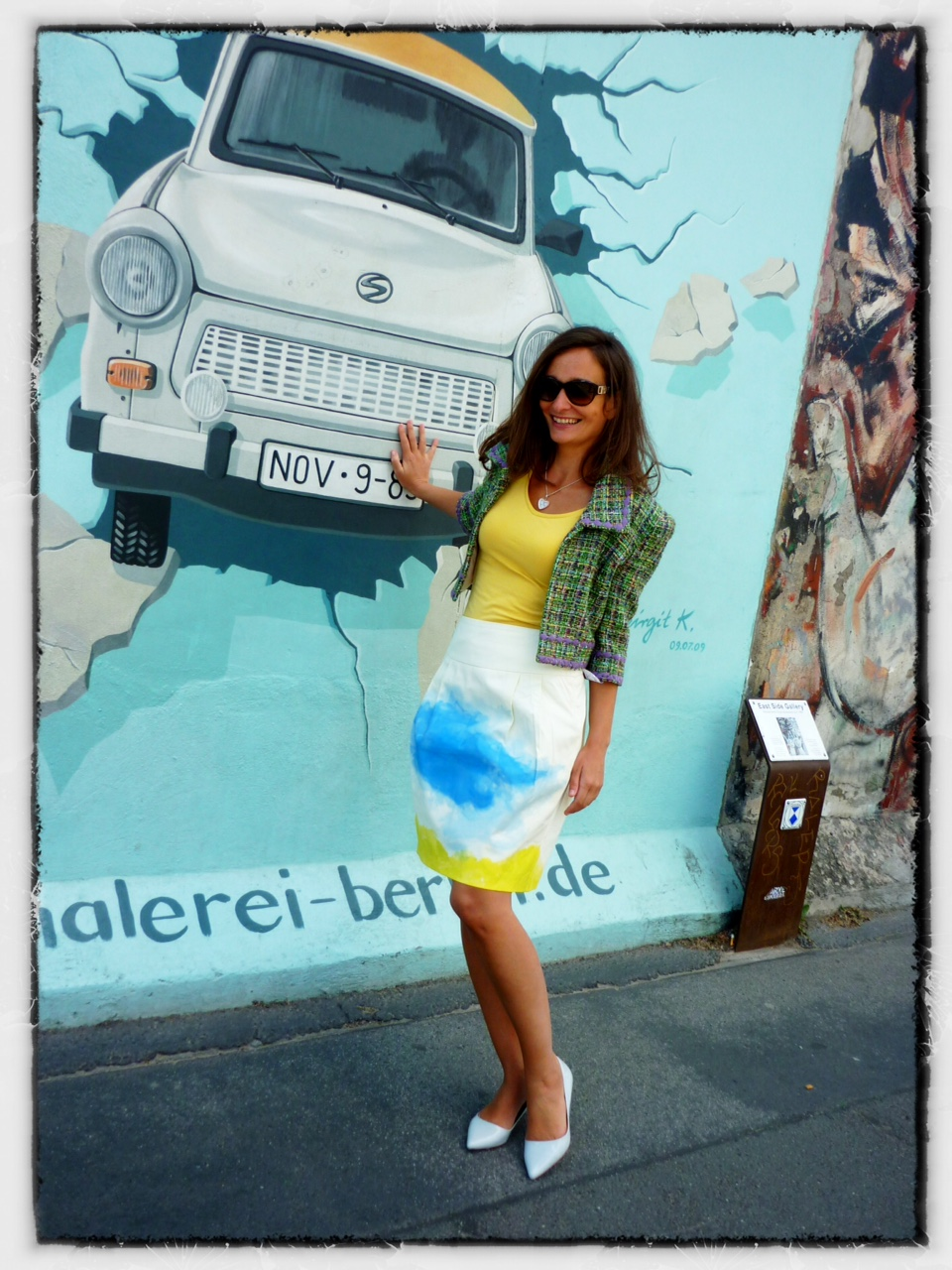 "At the Berlin Wall, with a ""Trabi"" symbolically breaking through the wall."