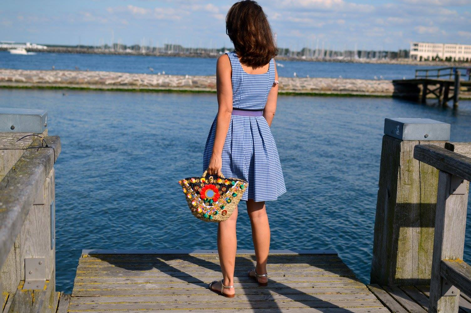Vichy gingham Dress. Straw bag at Baltic Sea
