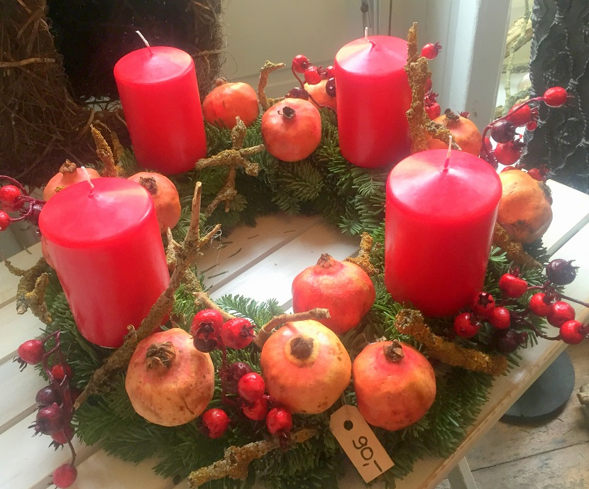 Advent wreath adorned with real pomegranates, iced berries and branches.
